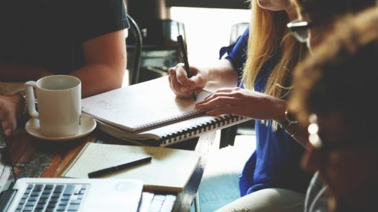 Symbolbild: Junge Menschen sitzen an einem Tisch und entwickeln gemeinsam Ideen und Projekte